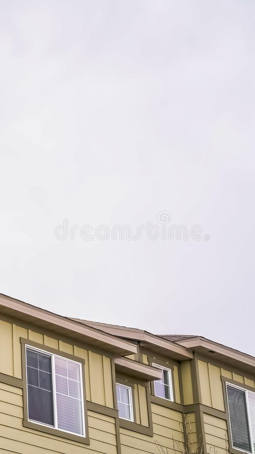 Vertical frame Close up view of exterior of homes with cream wall under sky filled with clouds. White blinds can be seen behind the sliding glass windows stock photo