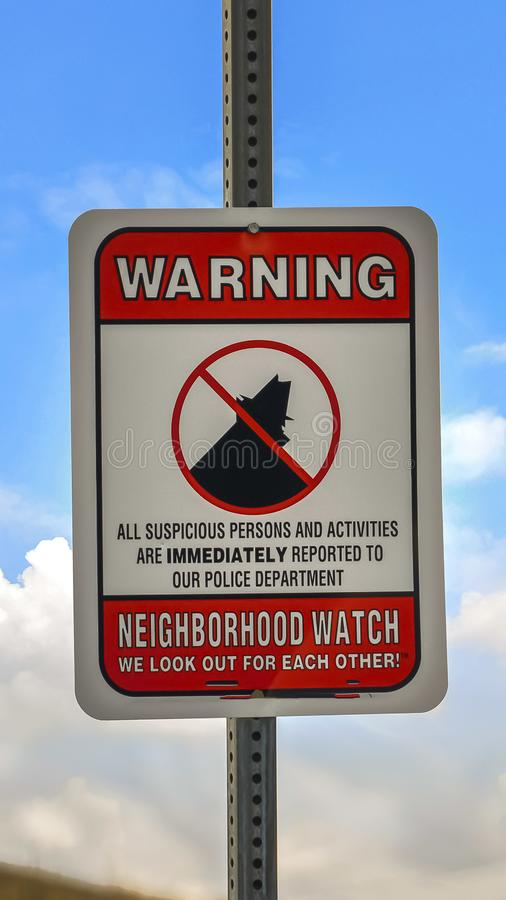Vertical frame Close up of a Warning sign on a neighborhood against cloudy blue sky background. The sign gives a warning that suspicious persons and activities stock photos