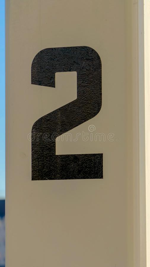 Vertical frame Close up of white rectangular posts with numbers painted on the surface. Building and sky cna be seen in the blurry backgroun on this sunny day royalty free stock photography