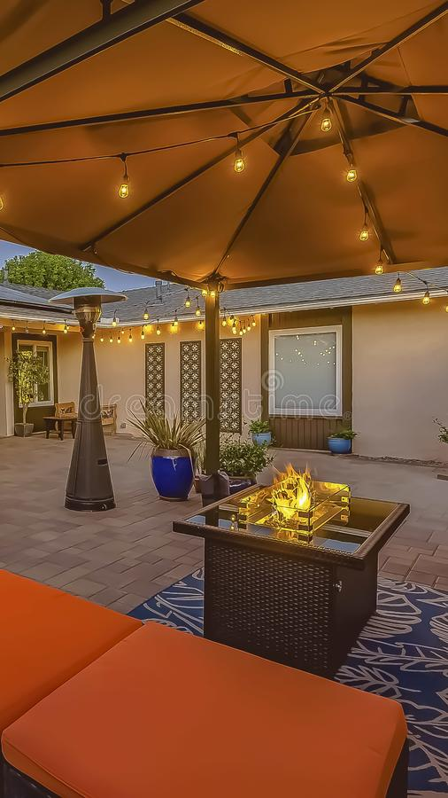 Vertical frame Cozy brick patio of a home with colorful seating area under a pavilion. A dining area under an umbrella can be seen near the house and brown royalty free stock photos