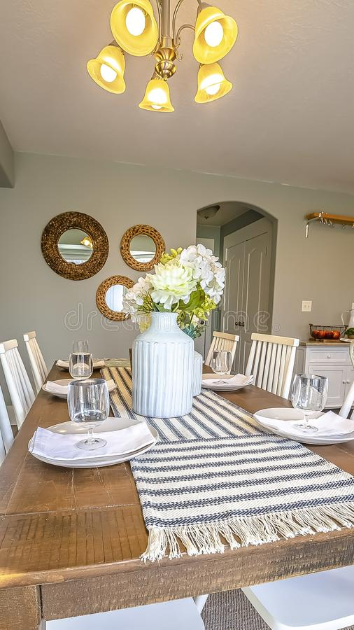 Vertical frame Dining room interior of a home with brown wooden table and white chairs. A chandelier is mounted on the ceiling above the table runner, flowers royalty free stock photos