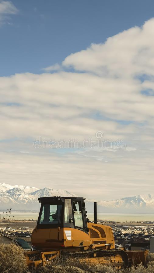 Vertical frame Empty yellow loader on a hill with view of the lake and snow topped mountain. Houses on a residential area in the valley can also be seen under royalty free stock photos