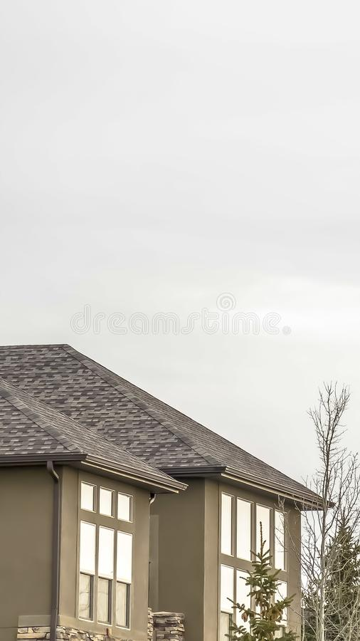 Vertical frame Exterior of home with stone brick and concrete wall against bright cloudy sky. Conifers and trees with leafless branches can be seen in front of stock photo