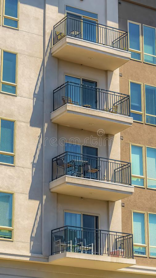 Vertical frame Exterior of a residential building with small balconies viewed on a sunny day. White blinds can be seen inside the rectangular glass windows stock photo