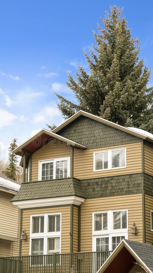Vertical frame Exterior view of a house with balcony and snow covered roof in winter royalty free stock images