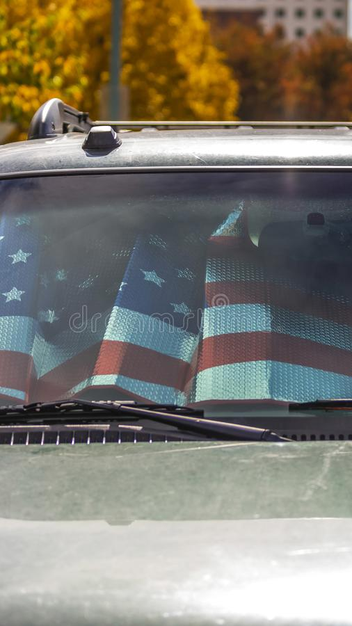 Vertical frame Front view of a shiny gray vehicle against lush trees on a sunny autumn day. Inside the vehicle is a sunshade with an American flag design royalty free stock photos