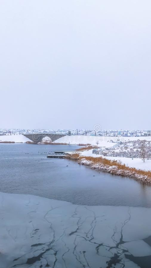 Vertical frame Frosty nature secnery with a lake surrounded by snowy terrain in winter. Arched bridge and houses can be seen in the distance against the cloudy stock photos
