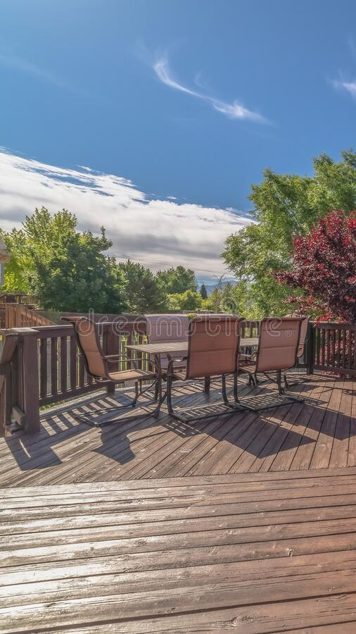 Vertical frame Furniture on the balcony of home with brown wooden floor railing and stairs. The outdoor living space has a scenic view of the yard, trees, and royalty free stock photos
