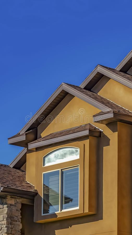 Vertical frame Home with concrete and stone exterior wall against clear blue sky on a sunny day stock photos
