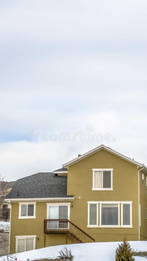 Vertical frame Home facade with stairs leading to the small balcony with overcast sky overhead. The surrounding area is blanketed with snow on this cold winter stock photography