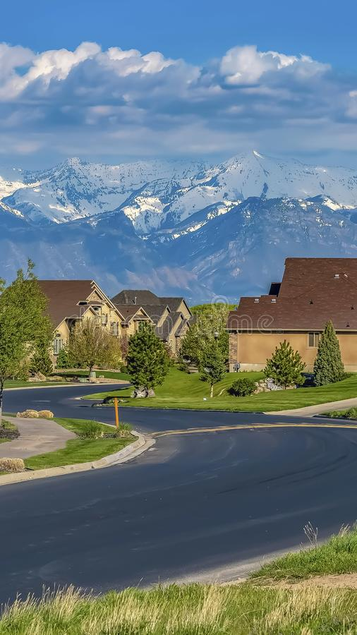Vertical frame Houses with landscaped yards along a curving road viewed on a sunny day. The residential area has a view of distant snow capped mountain against royalty free stock photo