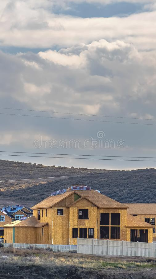 Vertical frame Houses under construction with overcast blue sky overhead. Road built on a hill covered with bushes can be seen in the background stock photos
