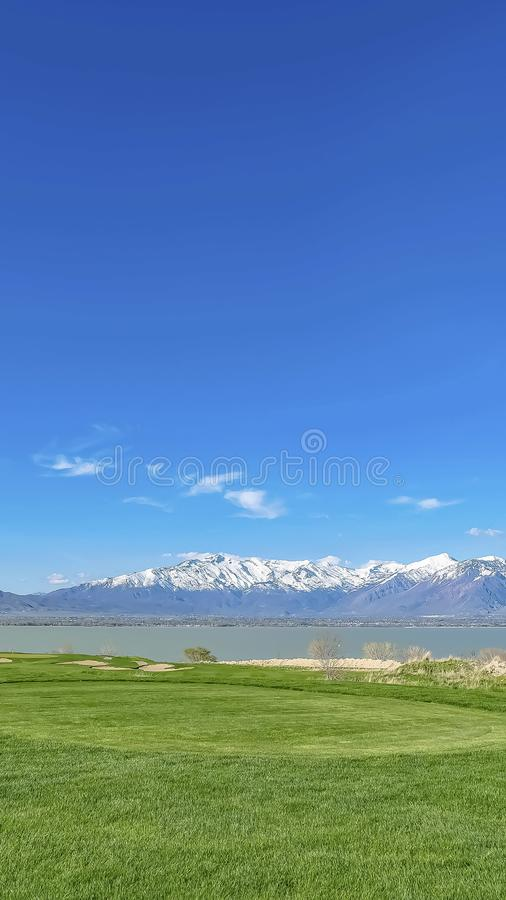 Vertical frame Lush grassy terrain with view of a calm lake and towering snow topped mountain. Lakefront homes can also be seen with blue sky overhead on a stock photos