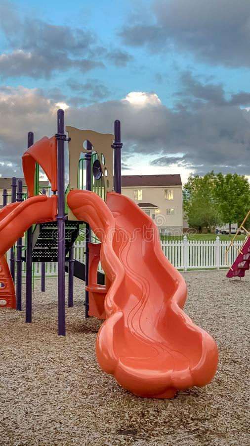 Vertical frame Neighborhood playground with bright colorful slides and swings under cloudy sky. Multi storey homes, trees, and vast field can be seen in the stock photo