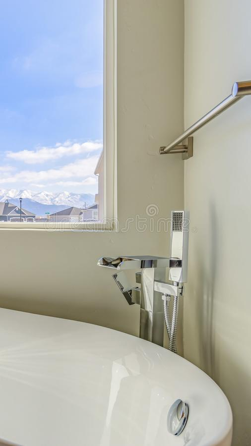 Vertical frame New house with a gleaming white bathtub inside the sunlit bathroom. The sliding window provides a scenic view of houses, snow capped mountain royalty free stock photos