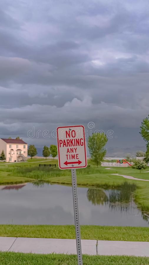 Vertical frame No Parking At Any Time sign with pond grassy terrain and homes in the background. The sky filled with gray clouds can be seen over the stock images