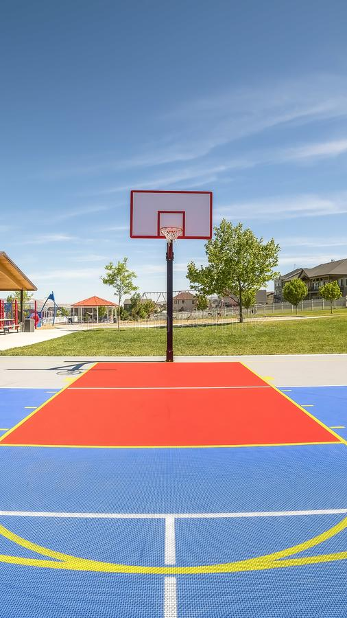 Vertical frame Outdoor basketball court at a park with picnic pavilion and childrens playground. The recreational area has a view of homes, lake, and mountain stock image