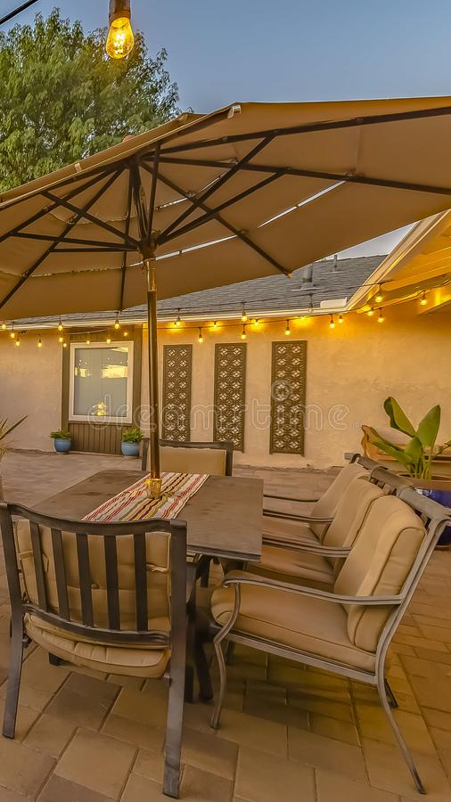 Vertical frame Outdoor dining and seating area on the cozy stone patio of a home stock photography