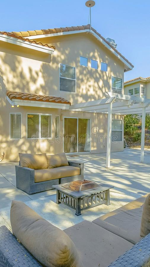 Vertical frame Outdoor seating area on the patio of a house lit by sunlight on this sunny day stock photography