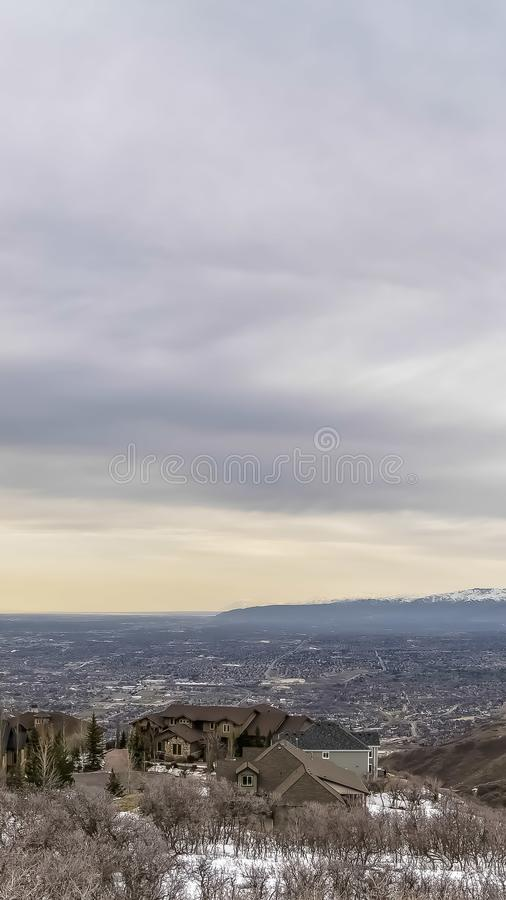 Vertical frame Panoramic view of a valley amd mountain under vast cloud filled sky in winter. Multi storey homes and paved road are constructed on the snowy stock image