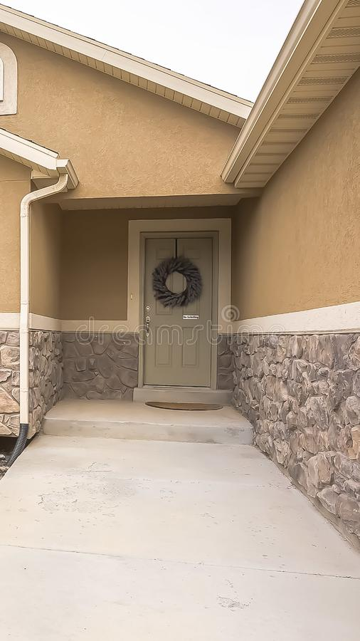 Vertical frame Pathway lined with bollard lights and leading to the front door with wreath. The yard and a combination of concrete and stone wall can also be stock photo