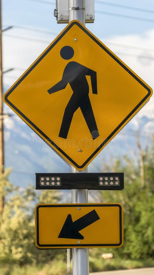 Vertical frame Pedestrian Crossing sign Crosswalk lights and Diagonal Arrow sign beside a road royalty free stock images