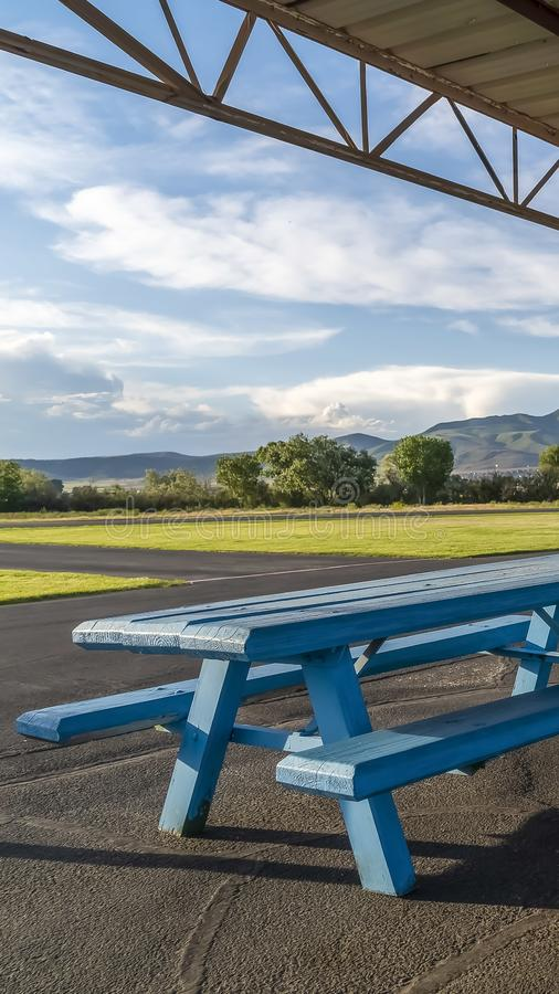 Vertical frame Picnic area with spool tables and blue wooden tables under a pavilion. Vertical frame Picnic area with spool tabled and blue wooden tables under a royalty free stock photography