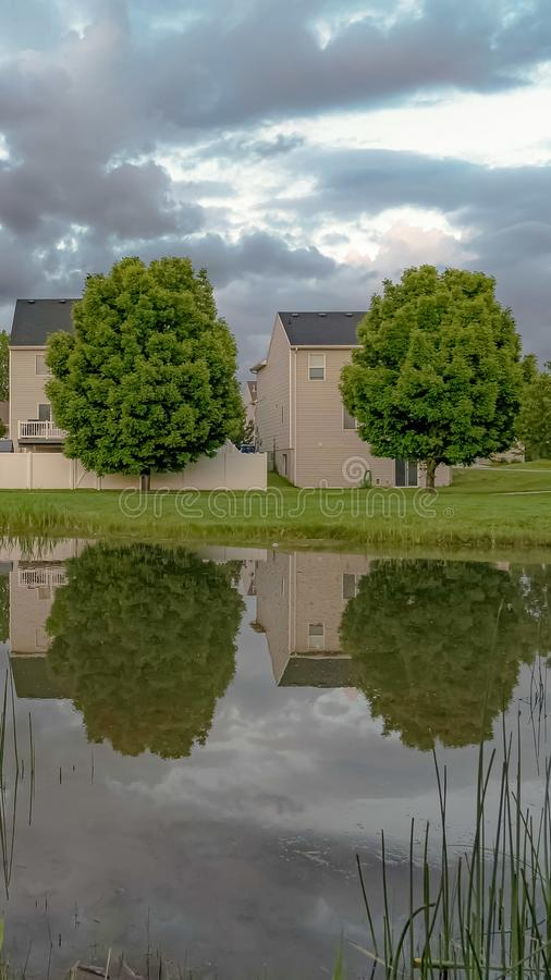 Vertical frame Pond with reflection of multi storey homes lush trees and cloud filled sky royalty free stock photo
