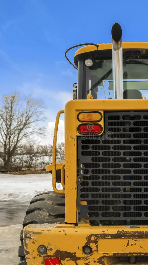 Vertical frame Rear view of a loader against snow covered ground and cloudy blue sky in winter stock photos