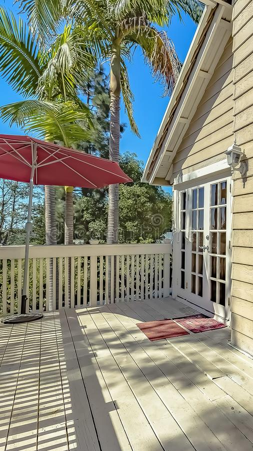 Vertical frame Red umbrella at the corner of the balcony of a house with wooden exterior wall. Lush trees can be seen against the clear blue sky on this sunny royalty free stock photos