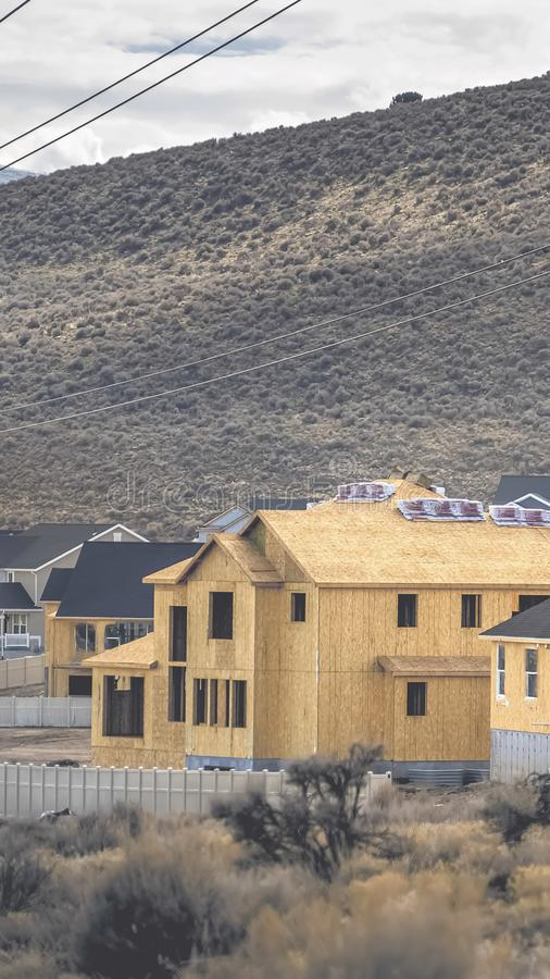 Vertical frame Residential area with view of the hill and cloudy sky in the background. The homes in the foreground are under going construction and have stock image