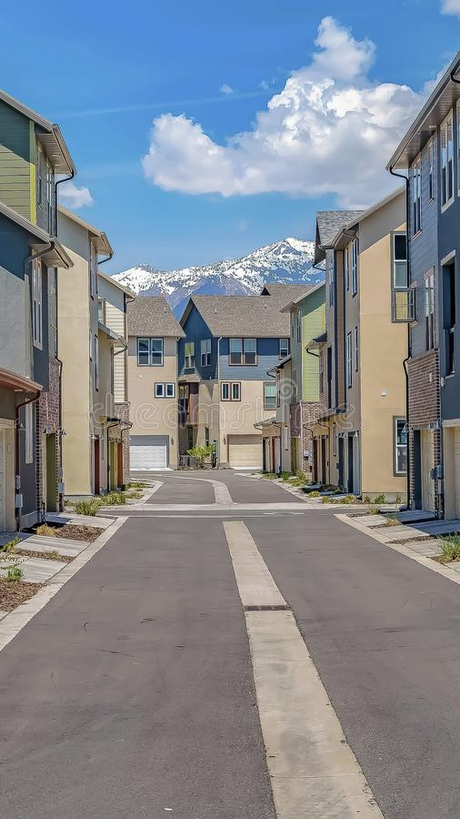Vertical frame Road in the middle of homes with view of snow capped mountain and cloudy sky stock photography
