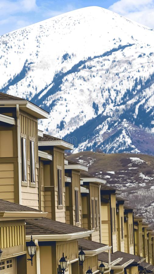 Vertical frame Row of homes with snow covered mountain and sky in the background. The houses have wooden exterior walls, outdoor lamps, and garage doors with stock photography