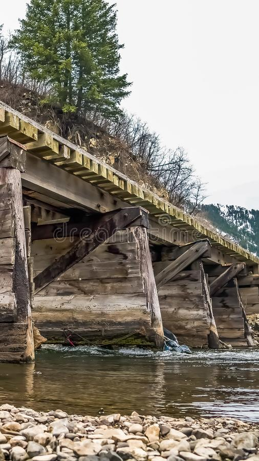 Vertical frame Rustic wooden bridge over a rocky stream with shiny water royalty free stock image