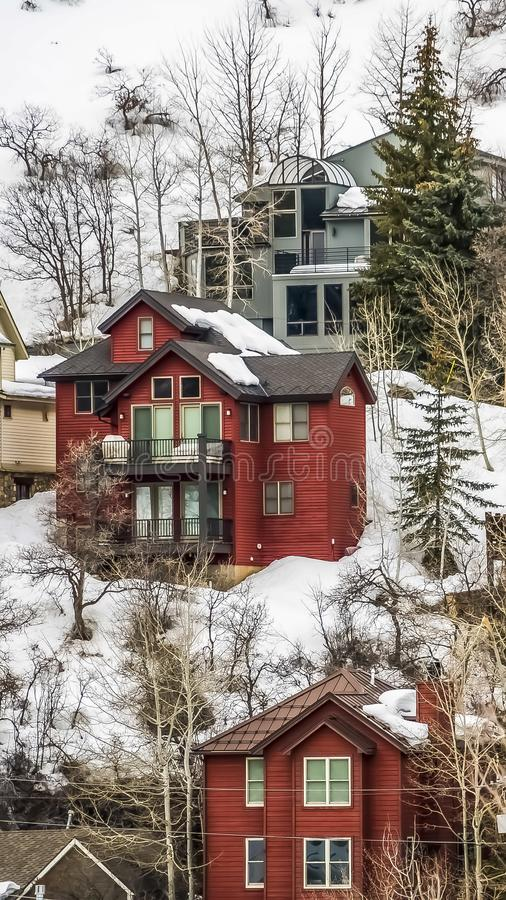 Vertical frame Scenic winter landscape with colorful houses built on the snowy mountain slope. The homes feature wood exterior walls and balconies royalty free stock images