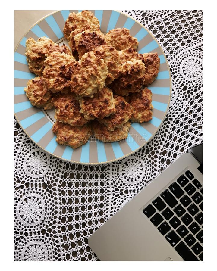 Vertical frame-shot of nuggets in a plate near laptop on the table. A vertical frame-shot of nuggets in a plate near laptop on the table stock photography