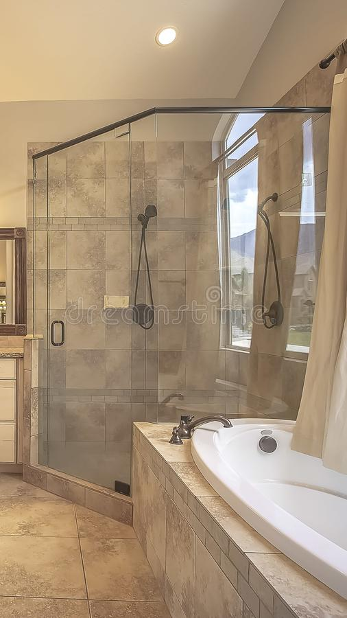 Vertical frame Shower stall beside an oval bathtub in front of an arched window with curtain stock image
