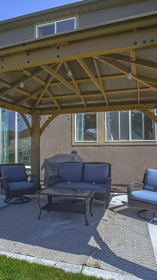 Vertical frame Table and chairs at a patio shaded by a pavilion with string of light bulbs. A small wooden garden shed can be seen beside the house royalty free stock images