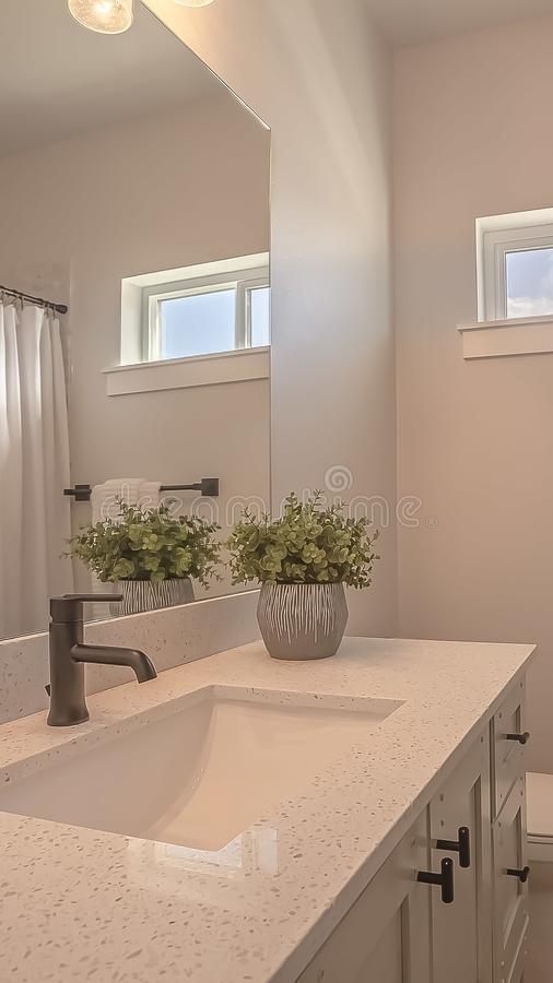 Vertical frame Toilet and vanity with cabinets and sink undermounted on the white countertop. The room also features a bathtub with shower curtain, small stock photos