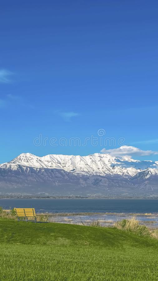 Vertical frame Vast grassy terrain with an empty bench overlooking a calm blue lake. Snowy mountain towering over the valley under blue sky can be seen in the royalty free stock image