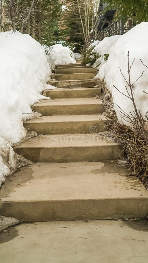 Vertical frame Weathered concerete outdoor steps amid snow covered slope in winter stock image