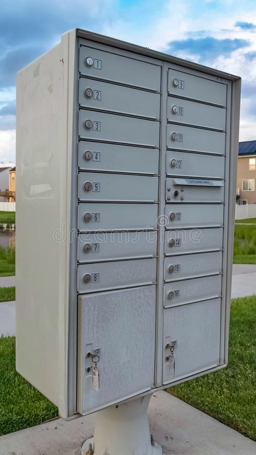 Vertical frame White metal cluster mailbox with pond grassy terrain and homes in the background. Cloudy sky and snow capped mountain can also be seen in this stock photo