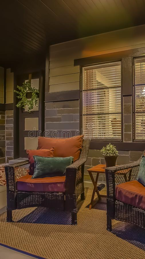 Vertical frame Wicker armchairs on the porch of a home with dark brick wall viewed at night. Carpets, wall decoration, wreath, and potted flowers can also be royalty free stock photography