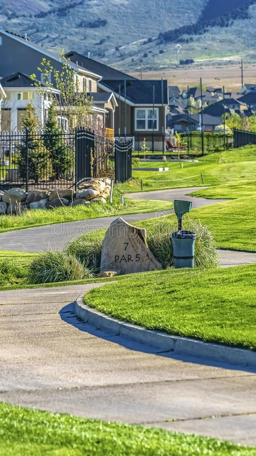 Vertical frame Winding pathway on a grassy terrain in front of houses viewed on a sunny day. The base of a towering mountain can be seen in the distance royalty free stock photos