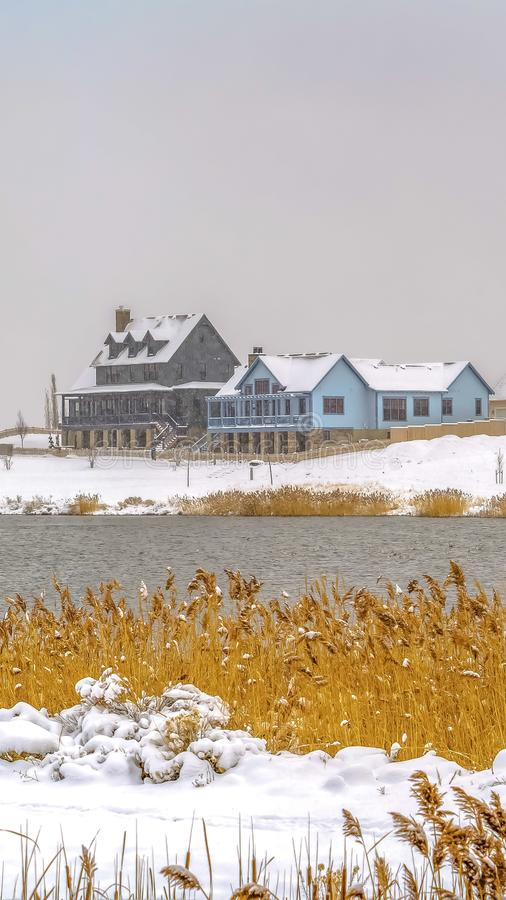Vertical frame Winter view of a lake suroounded by snow covered terrain and under cloudy sky. Arched bridge, decks, pavilion, and homes can also be seen around royalty free stock photography