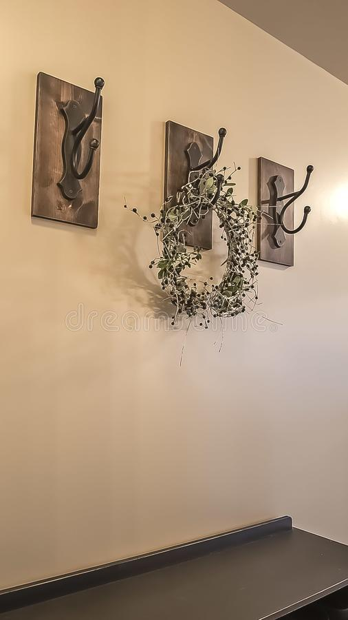 Vertical frame Wood cabinets and iron hooks against the beige wall of a home with white floor. A white floral wreath with small leaves hangs on one of the royalty free stock images