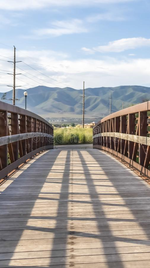 Vertical frame Wooden bridge with metal lattice guardrail over a lake with view of mountain stock image