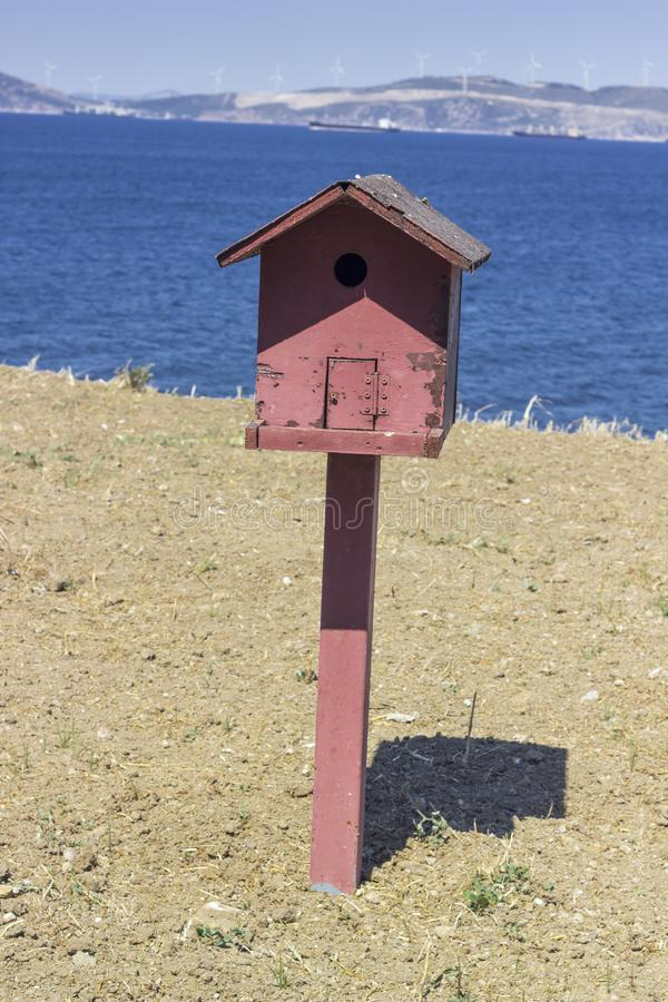 Vertical front close shot of colorful bird house near coastline at summertime stock images