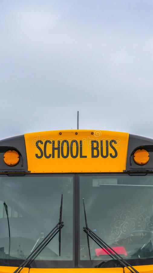 Vertical Front view of a yellow school bus with homes and cloudy sky in the background. Several side mirros and signal lights can be seen at the front of the stock images