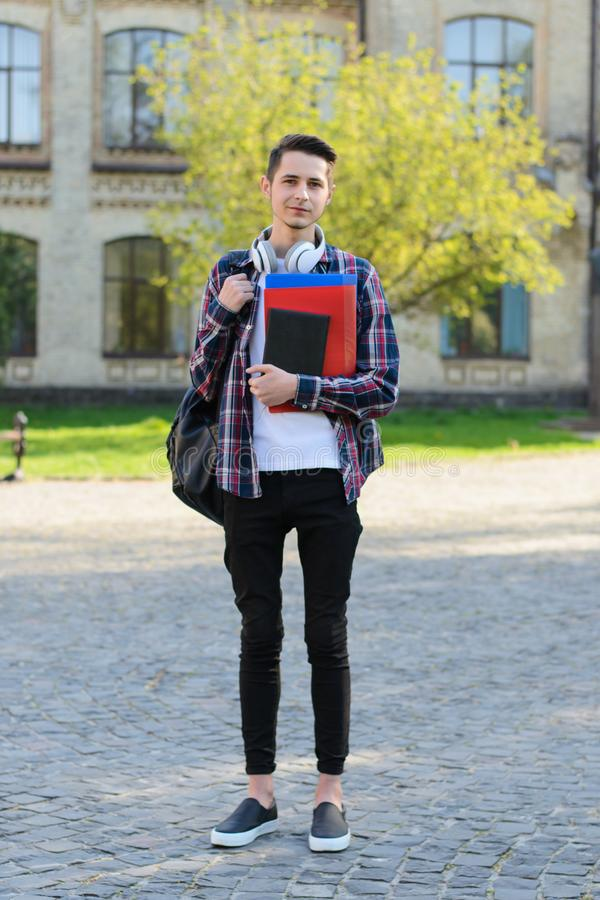 Vertical full length body size photo of cheerful confident kind friendly student studying abroad standing in front of campus royalty free stock photography